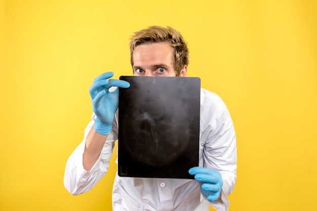 Вид спереди мужской врач, держащий рентген на желтом фоне, медик, хирургия, гигиена, covid
