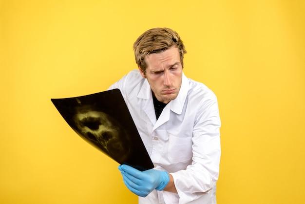 Medico maschio di vista frontale che tiene i raggi x sulla chirurgia dell'igiene del medico della scrivania gialla covid