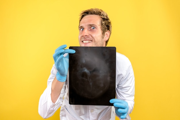 Front view male doctor holding x-ray on yellow desk medic surgery hygiene covid
