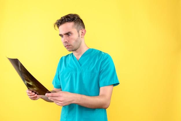Vista frontale del medico maschio che tiene i raggi x sull'emozione del medico dell'ospedale di salute del pavimento giallo