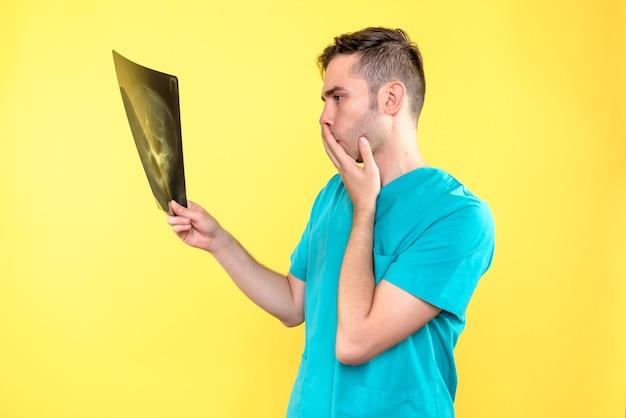 Vista frontale del medico maschio che tiene i raggi x sulla parete gialla