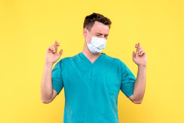 Vista frontale del medico maschio che spera sulla parete gialla