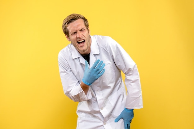 Front view male doctor hurt his hand on yellow background medic health covid pandemic