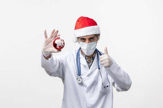 白い壁のウイルスcovid健康新年のおもちゃでマスクの正面図男性医師