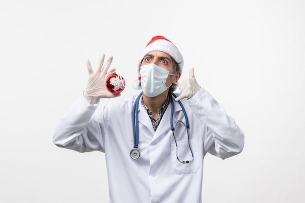 白い壁の健康ウイルスcovid新年のおもちゃでマスクの正面図男性医師