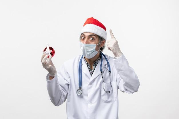 白い壁の健康covid休日ウイルスのおもちゃでマスクの正面図男性医師