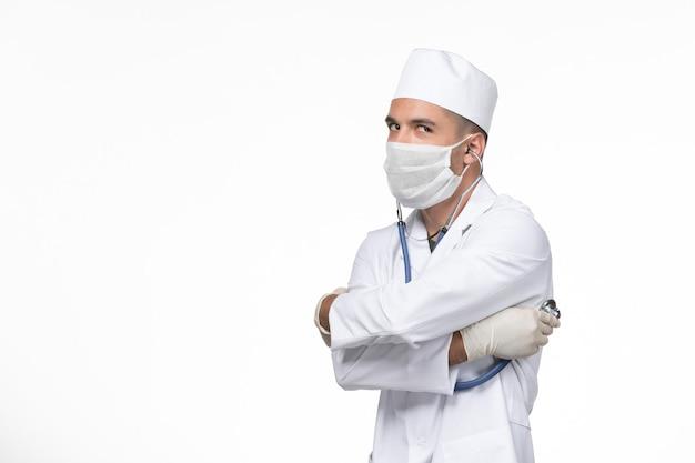 흰 벽에 청진기를 사용하여 코로나 바이러스에 대한 의료 소송 및 마스크의 전면보기 남성 의사 covid- virus 질병 질병 전염병