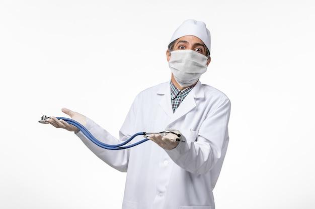 Вид спереди мужчина-врач в медицинском костюме и маске из-за коронавируса с помощью стетоскопа на светлой белой поверхности