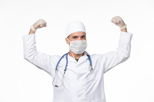 흰 벽에 covid- flexing으로 인해 의료 복을 입은 남성 의사와 마스크 착용 전면보기 covid- 바이러스 의학 유행병