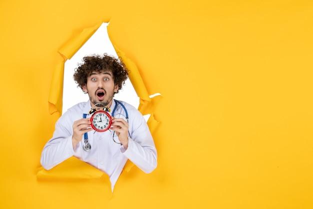 黄色の健康色病院の薬の買い物薬の時間に時計を保持している医療スーツの正面図男性医師
