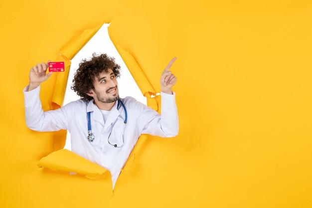 黄色の薬病院病ウイルス薬のお金の健康に赤い銀行カードを保持している医療スーツの正面図男性医師