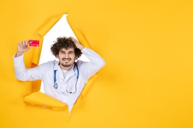 黄色の薬病院病ウイルス薬に赤い銀行カードを保持している医療スーツの正面図男性医師