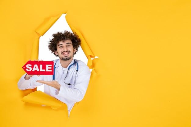 黄色の薬色健康病ショッピング薬に赤い販売を保持している医療スーツの正面図男性医師