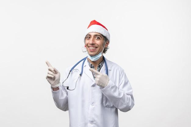 白い壁のウイルスの休日のcovid-感情の医療スーツの正面図男性医師