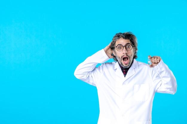 파란색에 작은 플라스크를 들고 의료 제복을 입은 전면 보기 남성 의사