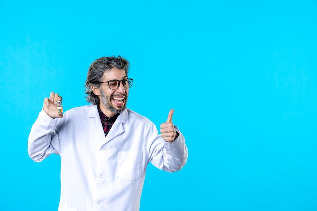 Вид спереди мужчина-врач в медицинской форме, держащий фляжку на синем