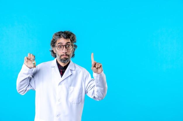 青に小さなフラスコを保持している医療制服の正面図男性医師