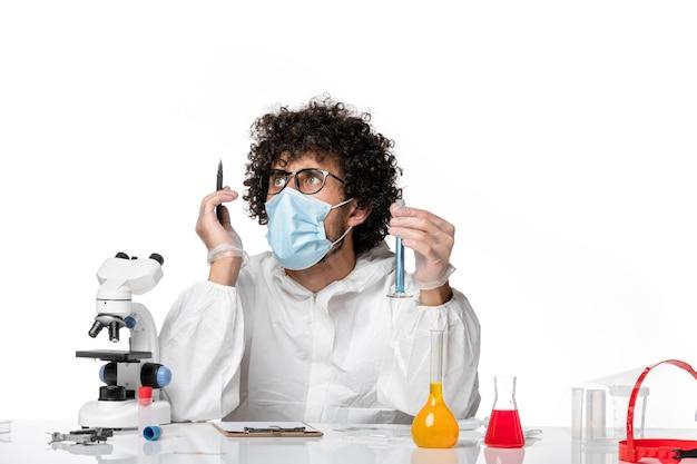 보호 복 및 마스크 흰색 배경에 쓰는 파란색 솔루션으로 플라스크를 들고 전면보기 남성 의사 대유행 covid- 전염병 바이러스