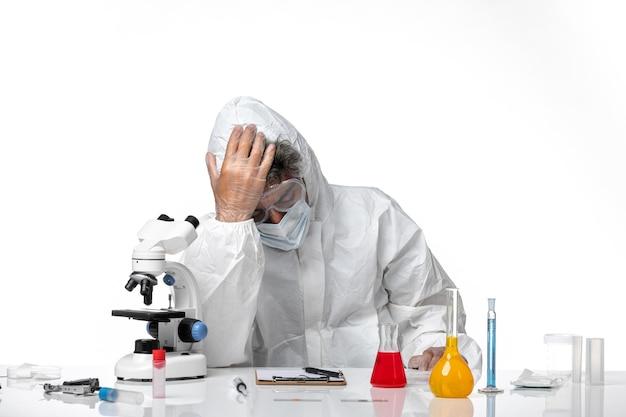 Вид спереди мужчина-врач в защитном костюме, чувствуя себя так усталым на белом