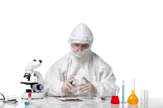 空のフラスコを保持し、空白に書いている防護服の正面図男性医師