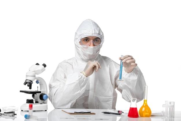 白い机の上に青い溶液と一緒にフラスコを保持しているため、マスク付きの防護服を着た男性医師の正面図