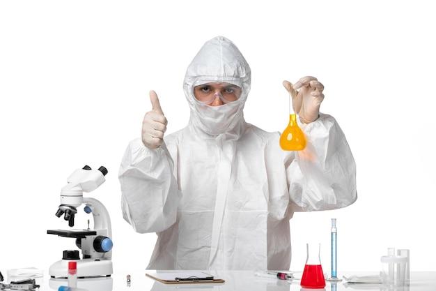 Вид спереди мужчина-врач в защитном костюме с маской из-за covid, держащего фляжку с желтым раствором на белом полу, пандемический вирус covid-health