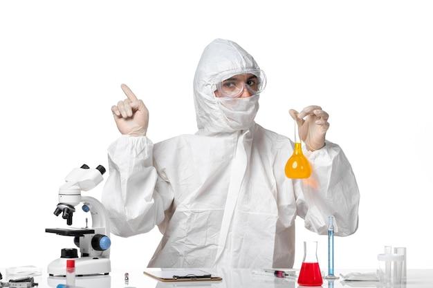 공백에 노란색 솔루션으로 플라스크를 들고 covid로 인해 마스크와 보호 복에 전면보기 남성 의사