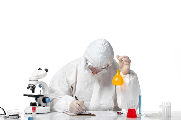Вид спереди мужчина-врач в защитном костюме с маской из-за covid, держащего колбу с желтым раствором на белом пространстве