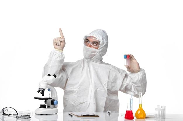 薄白色のスペースにフラスコを保持しているcovidのため、マスク付きの防護服を着た男性医師の正面図
