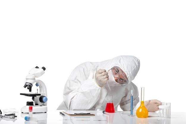 白い机の上のソリューションでcovid作業のため、マスク付きの防護服を着た正面図の男性医師