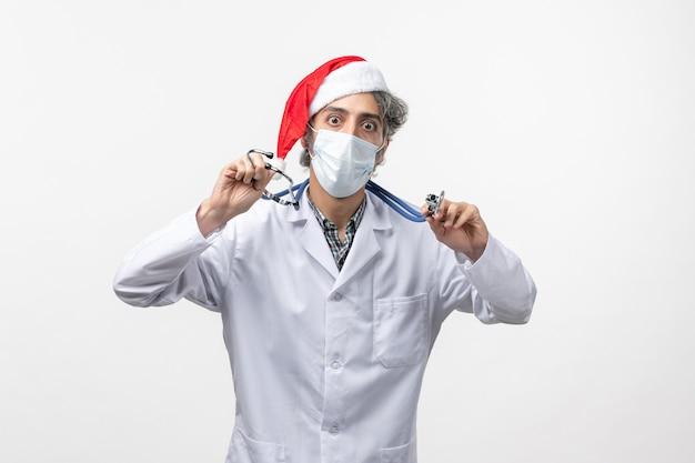 白い机の上の滅菌マスクの正面図男性医師covidウイルス元旦