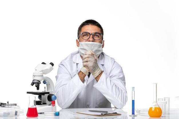 흰색 의료 양복과 마스크가 깊은 흰색 책상에 꿈꾸는 전면보기 남성 의사