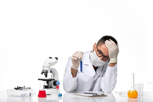 白い医療スーツと白いスペースに青いソリューションとフラスコを保持しているマスクと正面図男性医師