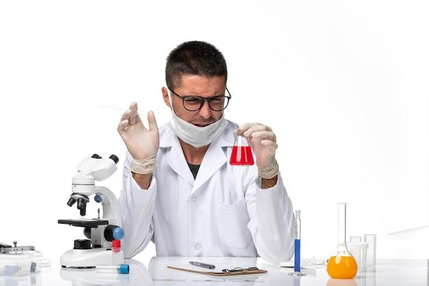 Вид спереди мужчина-врач в белом медицинском костюме и с маской, держащей красный раствор на белом пространстве