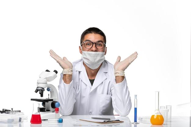 Вид спереди мужчина-врач в белом медицинском костюме и с маской на светлом белом пространстве