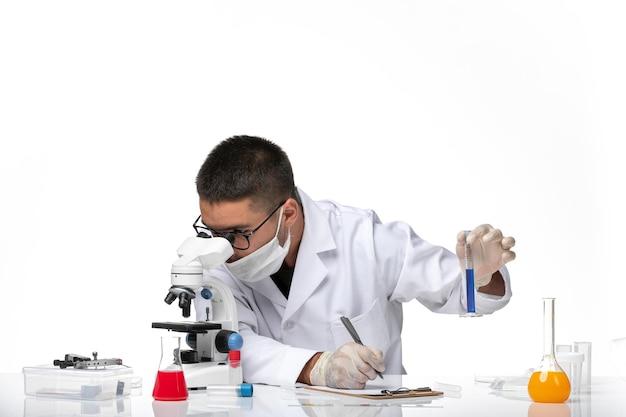 白い医療スーツと白いスペースで彼の顕微鏡を使用してマスクを使用して正面図の男性医師