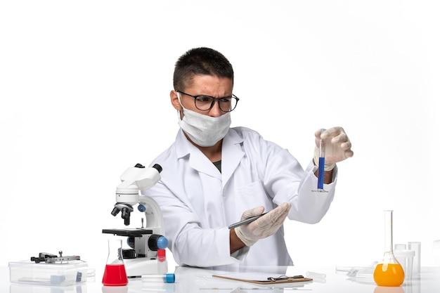 Вид спереди мужчина-врач в белом медицинском костюме и с маской, работающей с раствором на белом пространстве