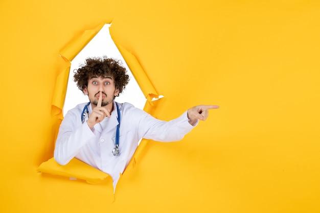 Вид спереди мужчина-врач в белом медицинском костюме на желтом разорванном лекарстве.