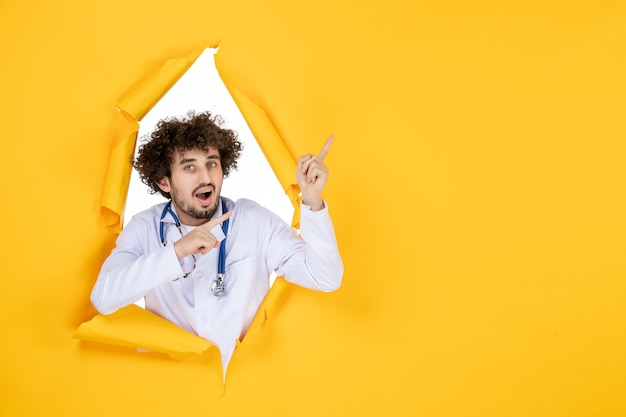 黄色の破れたウイルス薬の色の薬の健康に関する白い医療スーツの正面図男性医師