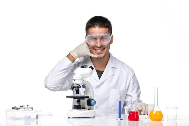 Вид спереди мужчина-врач в белом медицинском костюме сидит с решениями, улыбаясь на белом пространстве