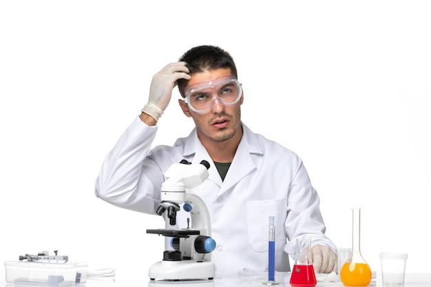 Вид спереди мужчина-врач в белом медицинском костюме сидит с решениями и думает на белом пространстве