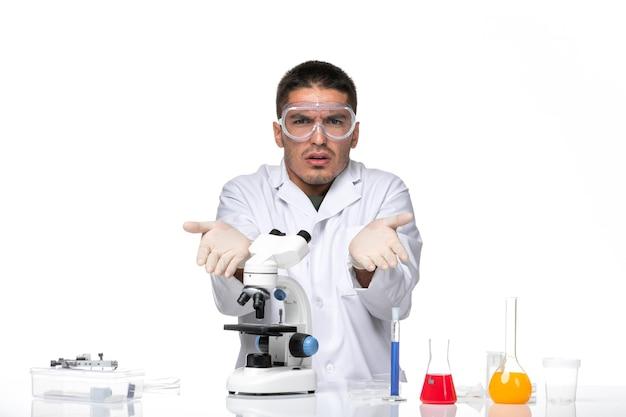 Вид спереди мужчина-врач в белом медицинском костюме, сидящий с растворами на белом пространстве