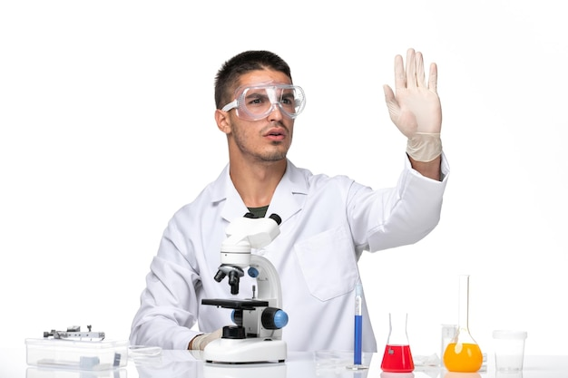 흰색 책상에 솔루션과 함께 앉아 흰색 의료 소송에서 전면보기 남성 의사