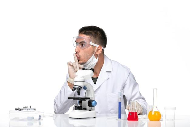 Вид спереди мужчина-врач в белом медицинском костюме с маской из-за covid на белом пространстве