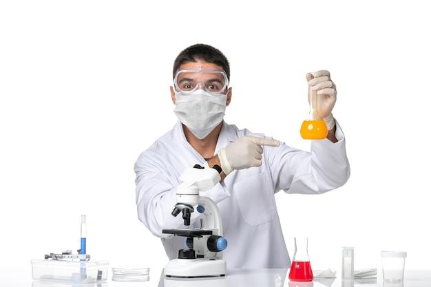 Вид спереди мужчина-врач в белом медицинском костюме с маской из-за covid, работающего с растворами на светлом белом пространстве