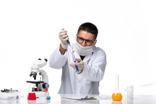空白のソリューションでcovid作業のため、マスク付きの白い医療スーツの正面図男性医師