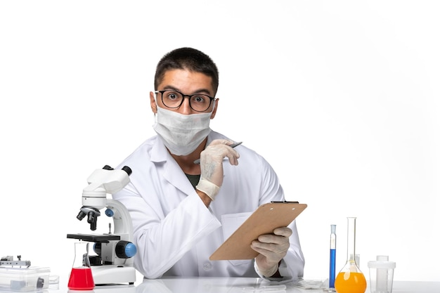 白いスペースにメモを書いているので、マスク付きの白い医療スーツを着た男性医師の正面図