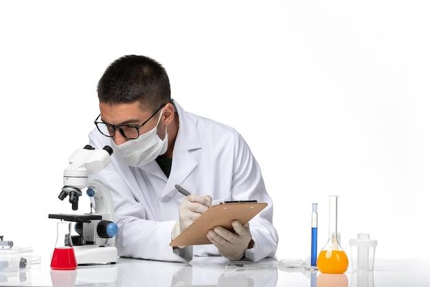 白いスペースで顕微鏡を使用して作業している白い医療スーツの正面図男性医師