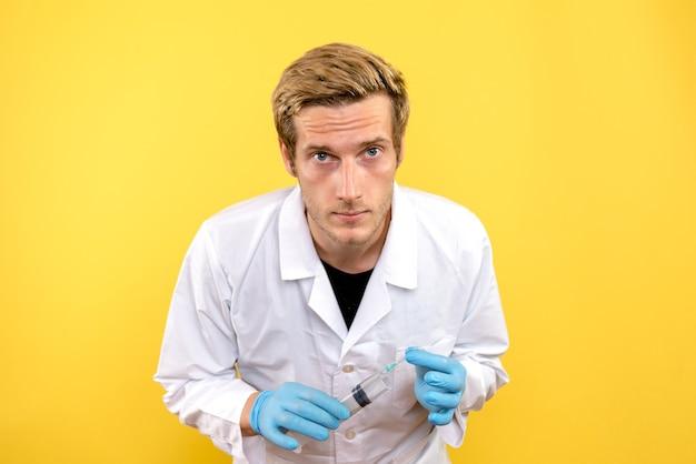 黄色の背景の薬用covid-感情ウイルスを見ているだけの正面図の男性医師
