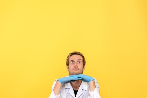 黄色の背景ウイルスcovid-感情薬を見ているだけの正面図男性医師